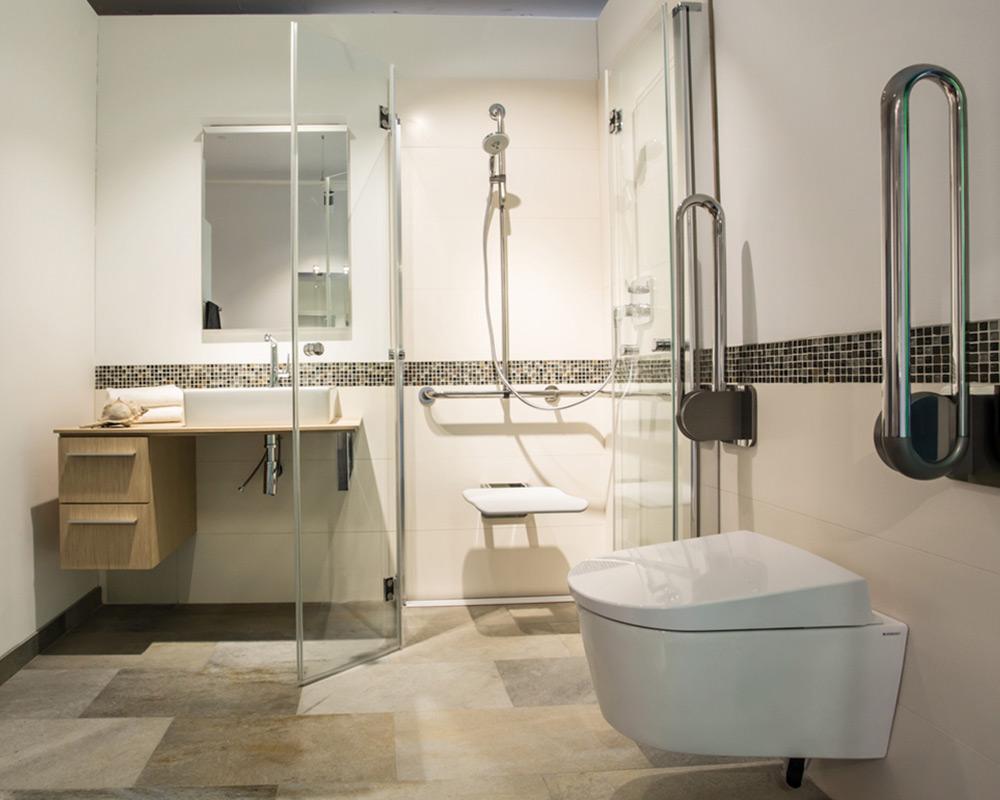 Barrierefreies Badezimer mit Dusche, Waschbecken und Toilette