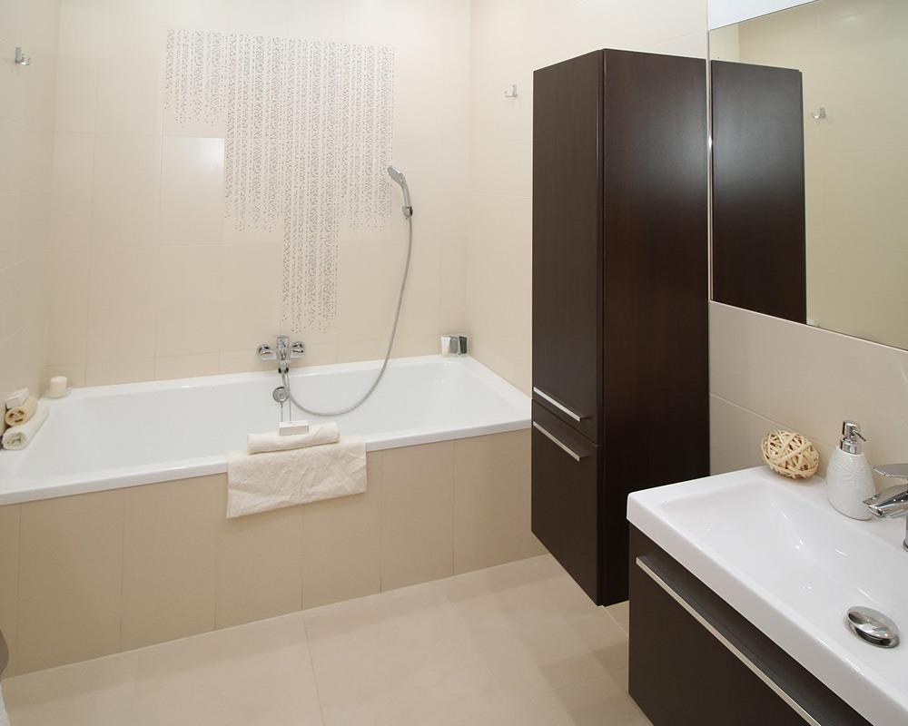 Badezimmer mit beigefarbenen Fliesen, Wanne und Badmöbeln