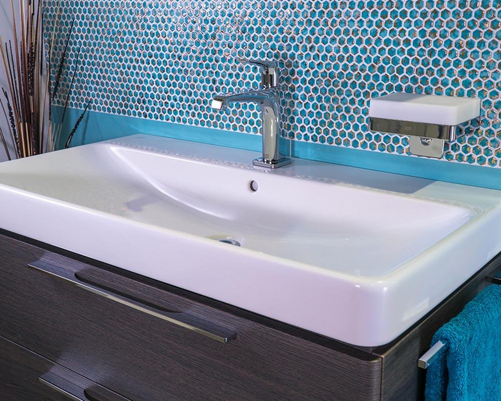 modernes, weißes Waschbecken mit Mosaikfliesenspiegel in Gold und Türkis