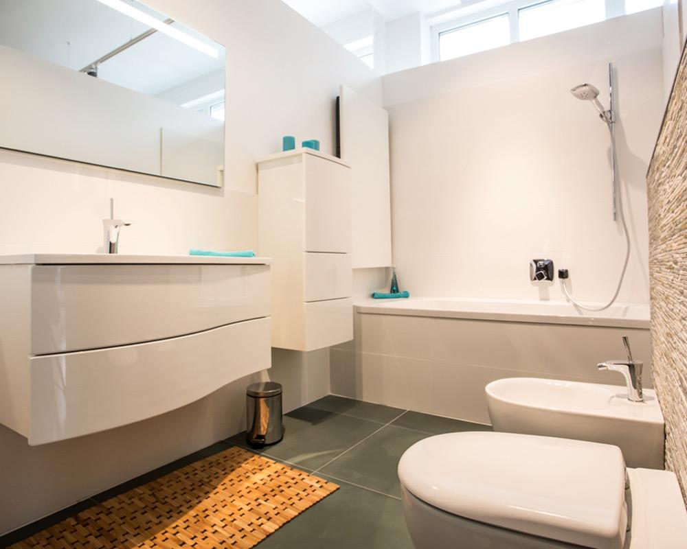 Referenz Schöffmann: Badezimmer mit weißen Möbeln, Wanne und Bidet